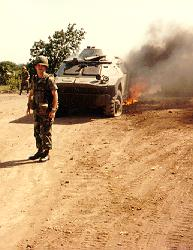 Armored cars, tires flat and burning from combat in Grenada against U.S. forces